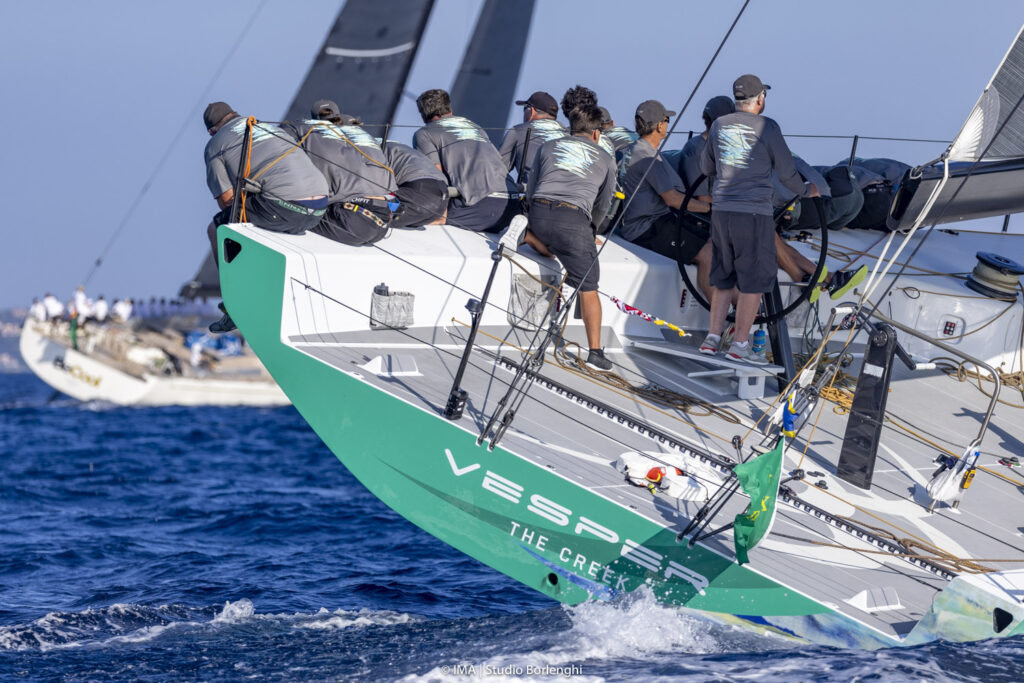 Behind Vesper, as she sails upwind with the crew on the side.