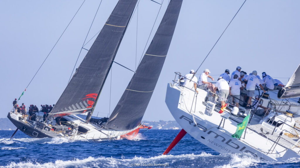 Comanche and Rambler 88 sailing almost side-by-side, upwind, both on a heal.