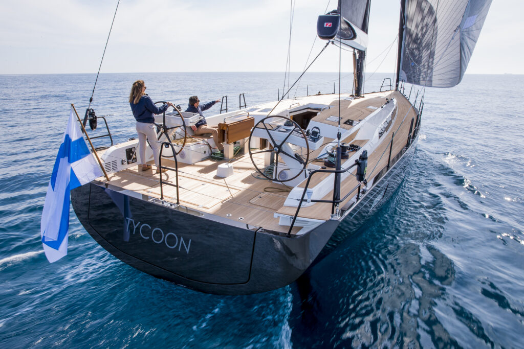 Swan 58 sailing on a reach, with a Greek flag out the back and the 2 crew enjoying the teak deck.