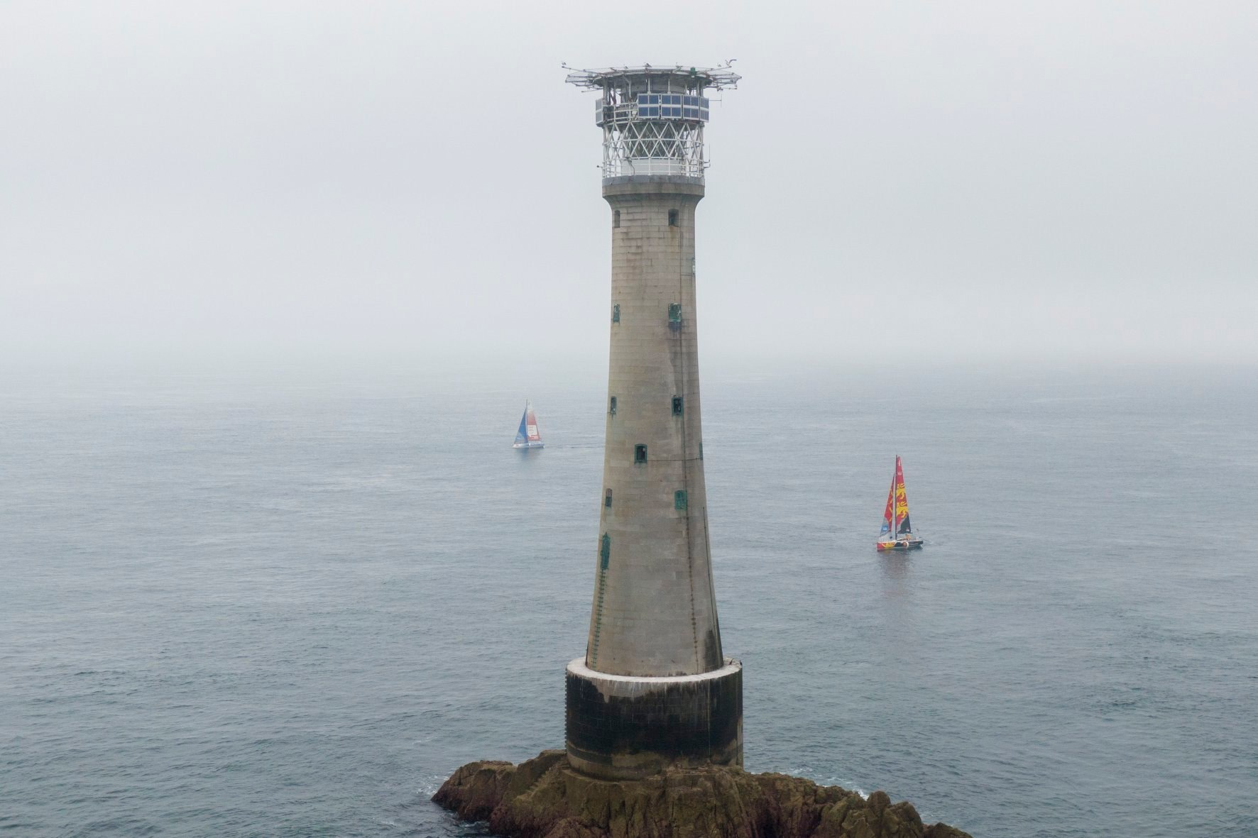 Aerial shot of 2 boats sailing past a lighthouse on a rock in foggy conditions.
