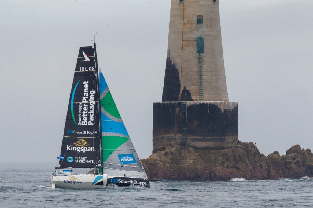 Tom Dolan's boat sailing past lighthouse on rock.