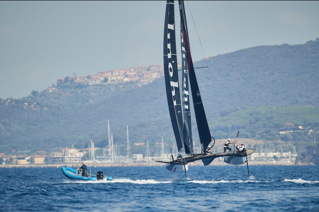 Alinghi on a reach, next to a powerboat.