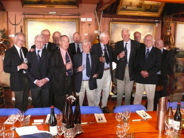 Former Admiral Cup sailors in front of the dinner table, smiling.