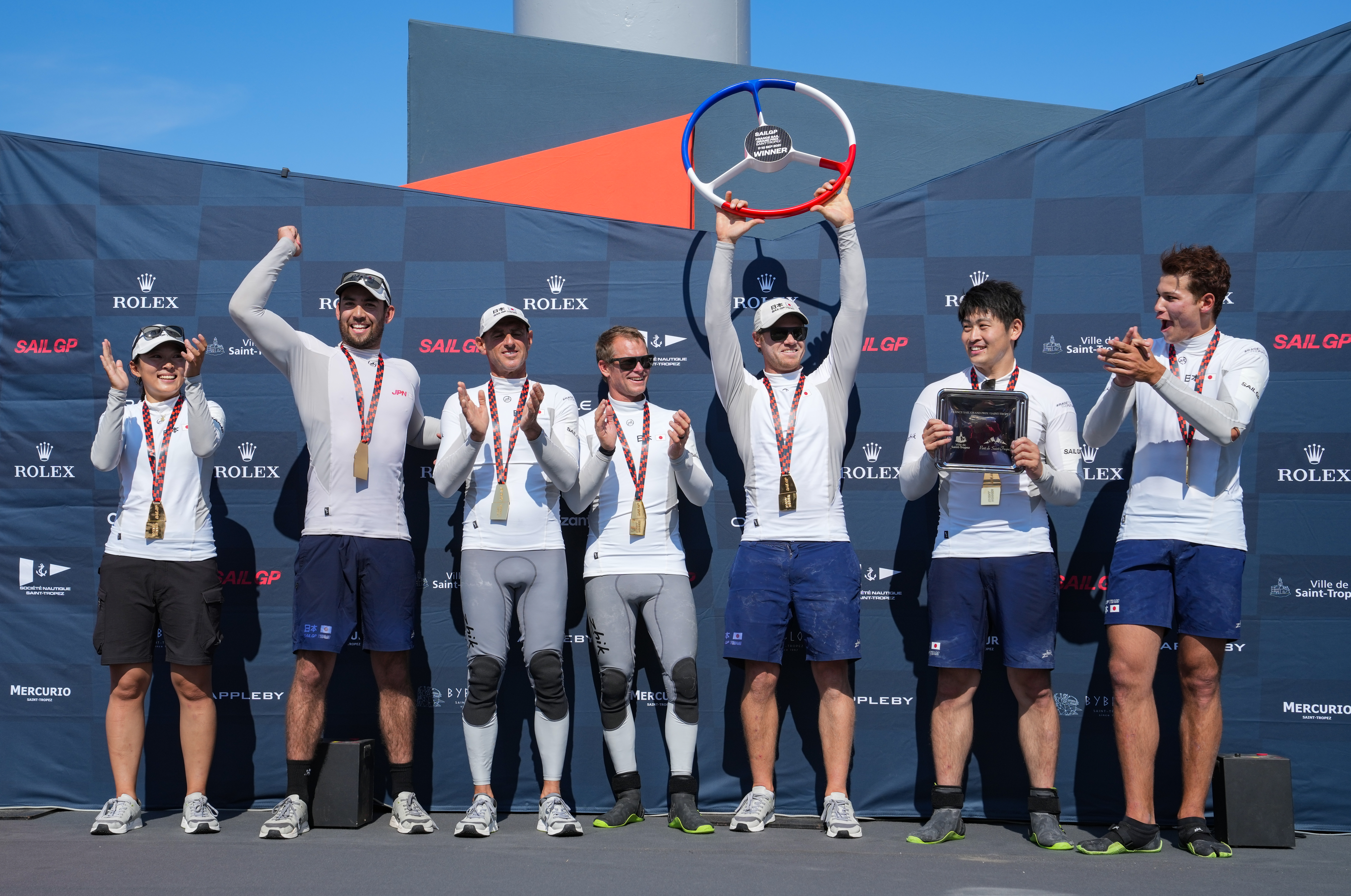 Team Japan on the stage with the steering wheel trophy.