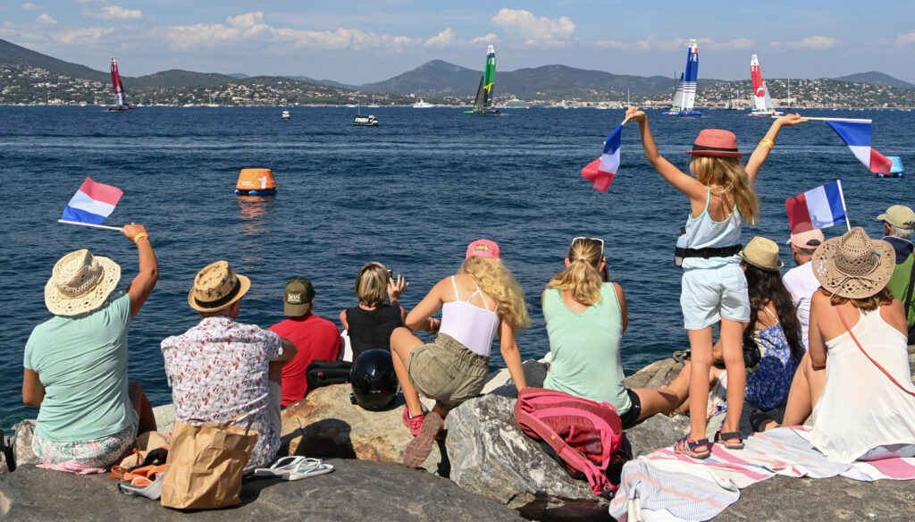 Spectators watching from the shore with French flags.