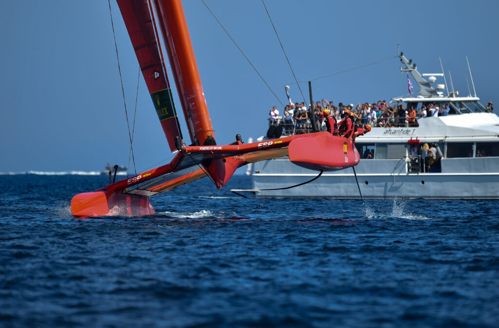 The Spanish Team healing, with a big spectator boat behind them. A crew member checking for damage.