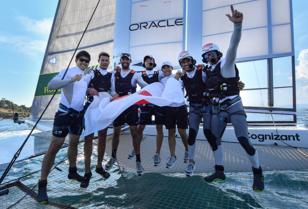 Japan SailGP Team hold the Japanese flag, celebrating their win on the boat.