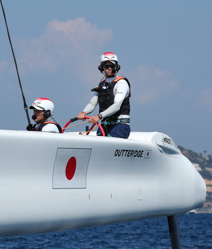 Nathan Outterridge with his helmet and headset on, steering the boat.