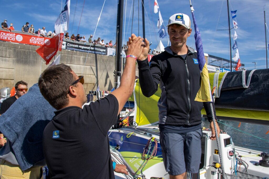 Pierre Quiroga high fiving a supporter on the dock from his boat.