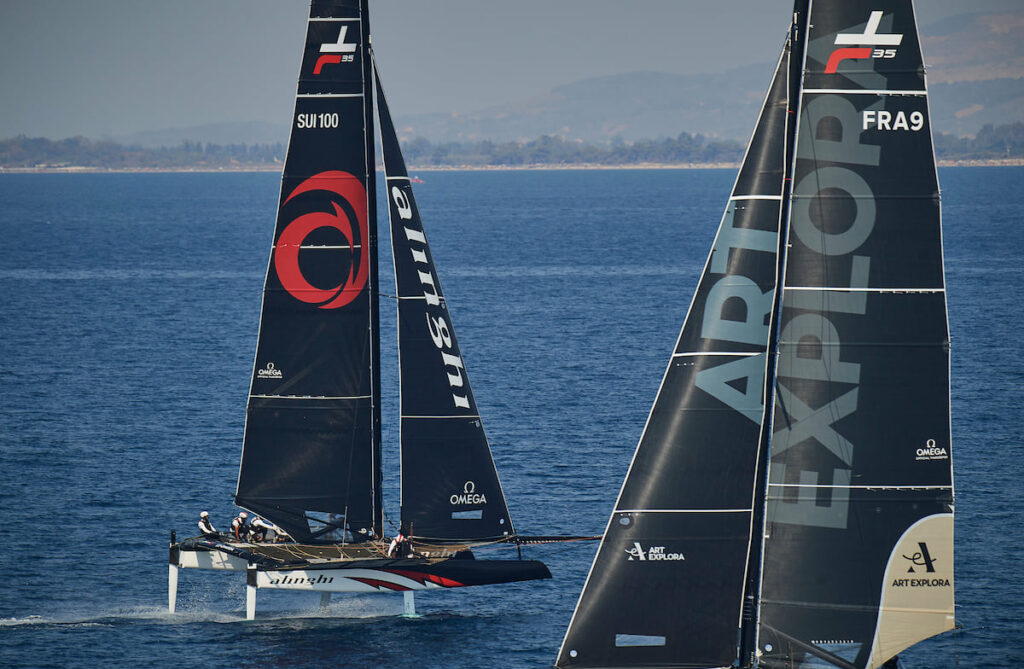 Alinghi sailing downwind, while a competitor sails upwind.