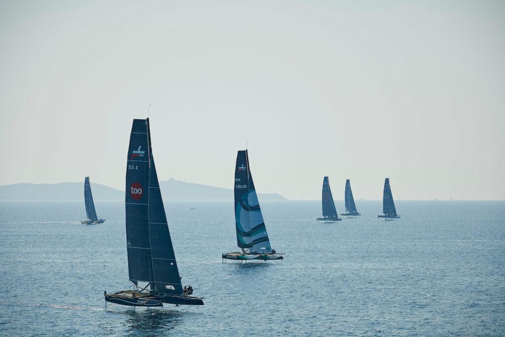 The fleet sailing upwind on a hazy day.