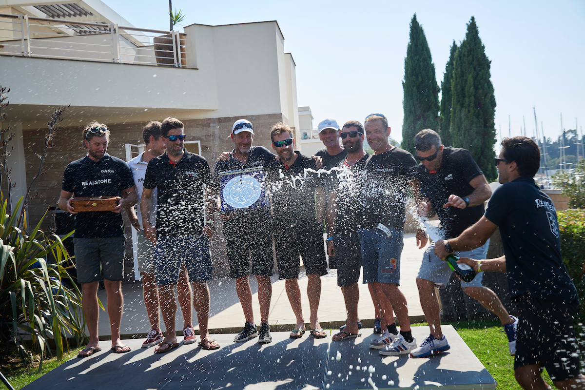 Realteam Sailing celebrating their win at the Awards Ceremony, spraying champagne.