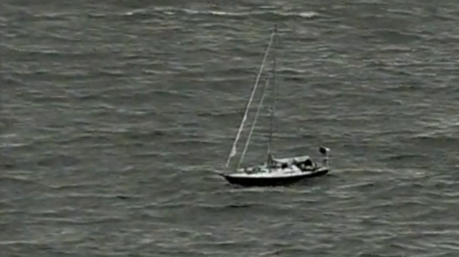 Aerial shot of blue yacht with no sails, surrounded by choppy water.