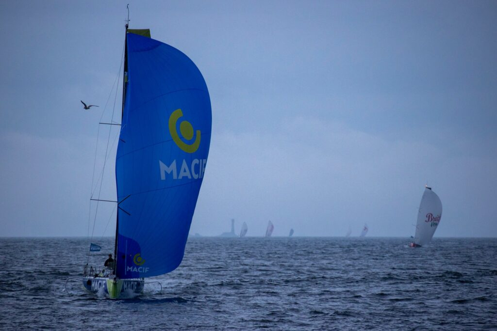 Pierre Quiroga sailing downwind with kite, with fleet and rock behind him. Quite foggy.