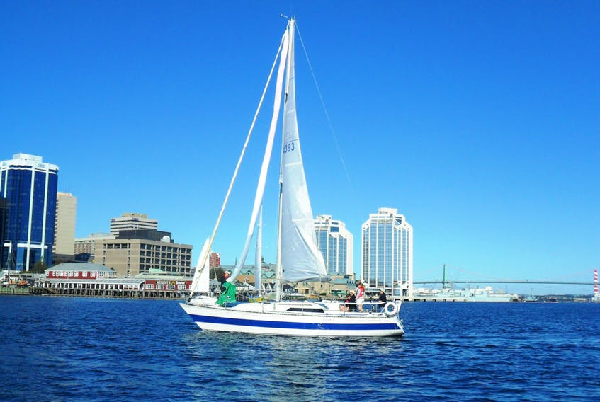 Yacht sailing with just the main. Someone is getting the spinnaker chute ready at the bow of the boat.