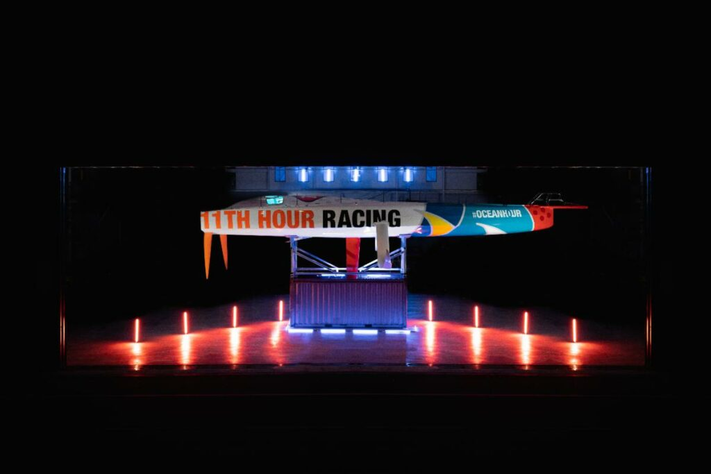 11th Hour Racing yacht on the hard stand, lit up by red lights.