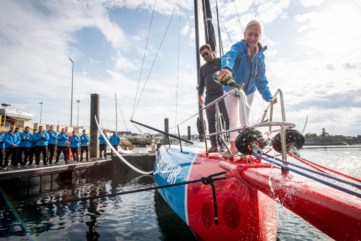 Woman pouring champagne over the bow of a red and blue yacht with a long bow sprit.