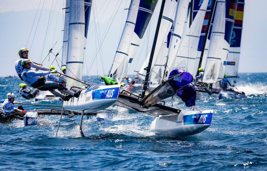 Jason Waterhouse and Lisa Darmanin sailing the nacra 17 on foils, followed by a bunch of boats.
