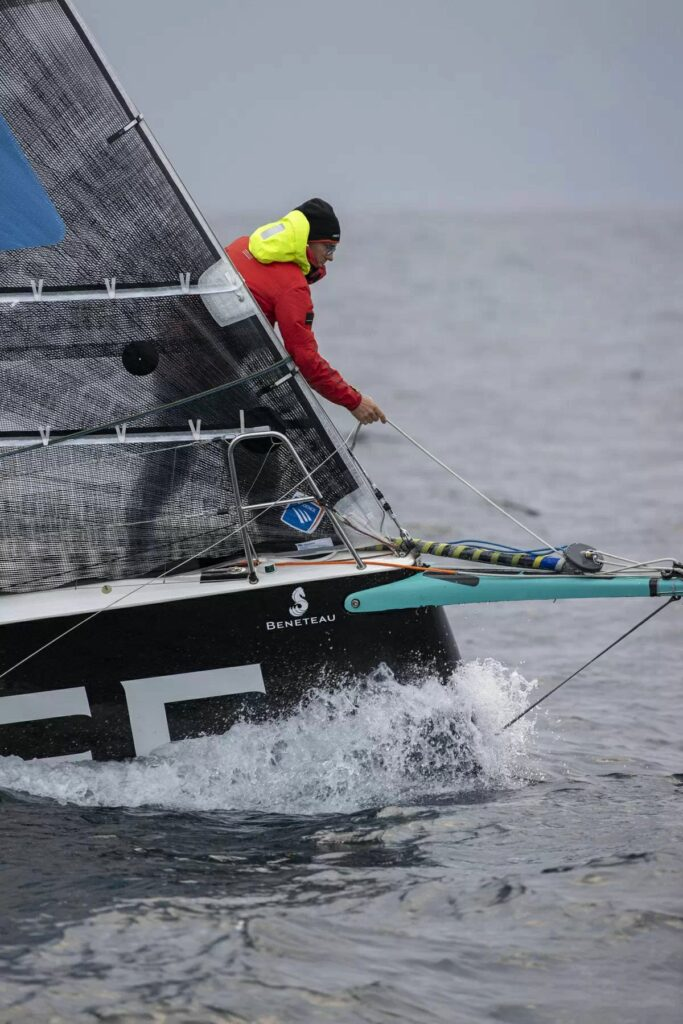 Xavier Macaire leaning over the bow sprit, where the foiling kite sits.