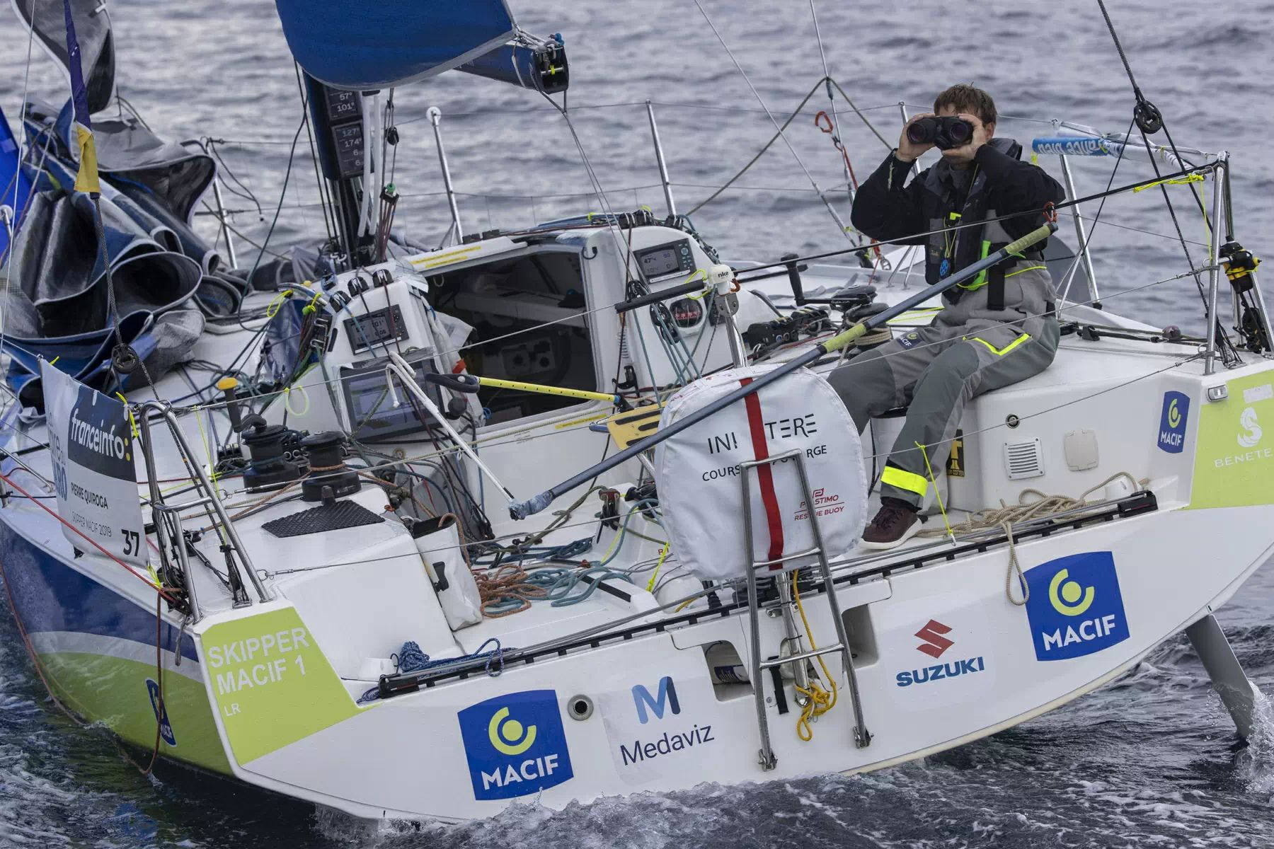 Pierre Quiroga sailing, with binoculars to his eyes.