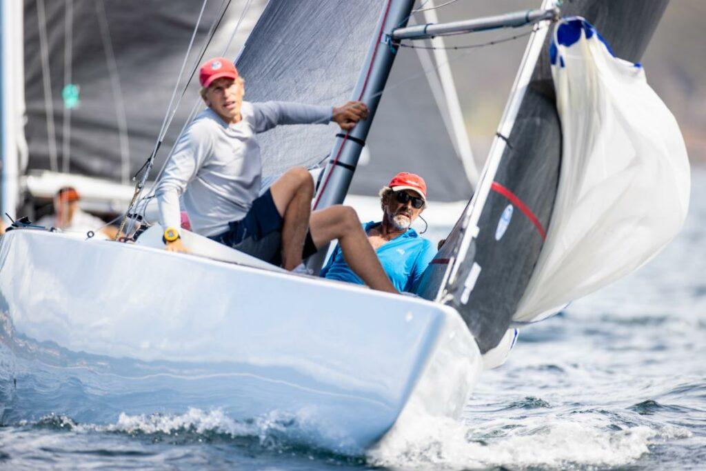 A white yacht sailing downwind, healing to leeward. Bow person preparing kite and skipper sitting to leeward, looking forward.