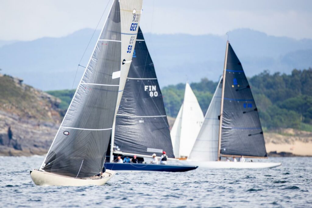 Five boats sailing upwind on different tacks, with a beach and rocky headland in the background.