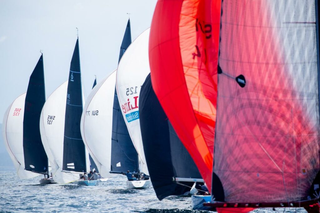 A fleet of boats line-up behind each other, sailing on a kite reach.