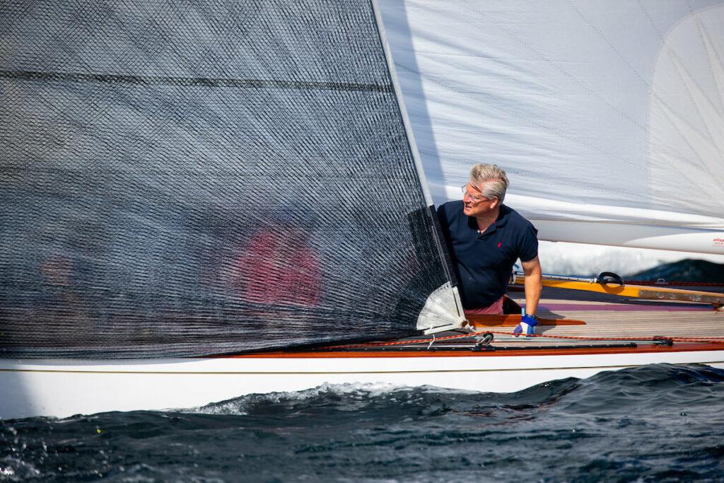 A skipper poking his head around the huge headsail.