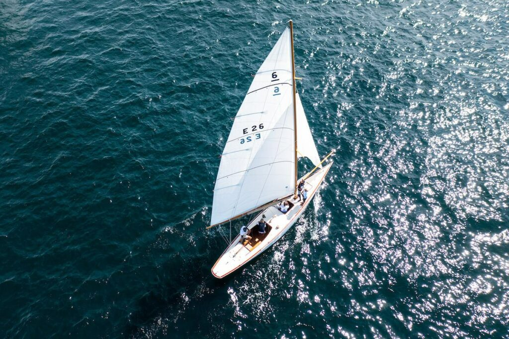 Aerial shot of a yacht sailing downwind with no kite. Bow crew are setting up pole.