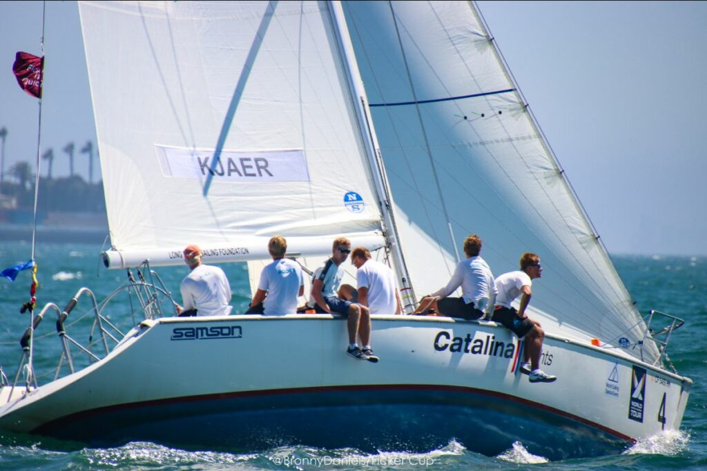 Emil Kjaer and crew sailing upwind, with some crew leaning over the side.