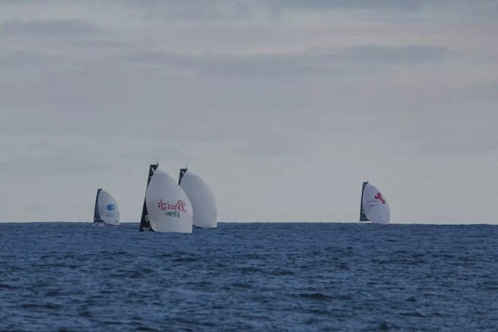 Four boats on a kite run, blocked partly by the swell.