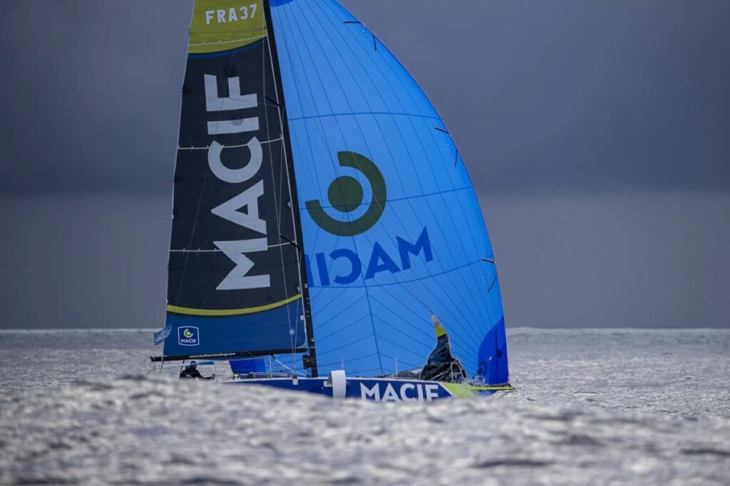 Pierre Quiroga sailing in big swell. We can only see half of the boat (the main sail and blue spinnaker).