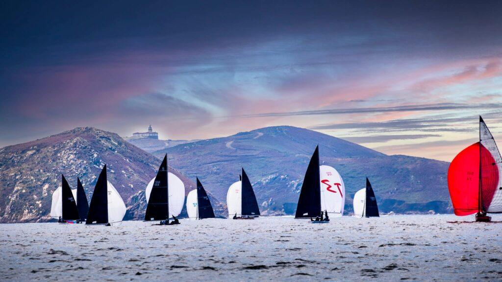 Fleet sailing on spinnaker run towards mountains and an orange and blue sky.
