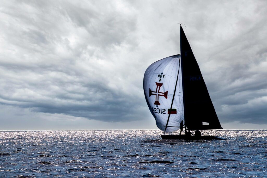 A boat on a spinnaker run, bow person standing in front of the mast. The clouds are dark, but the sun is glistening on the water.