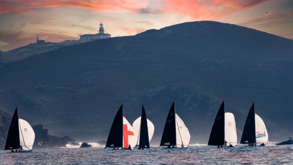 Six boats sailing on a spinnaker run towards a mountain with a church like building on top of the mountain. The sun looks to be setting.