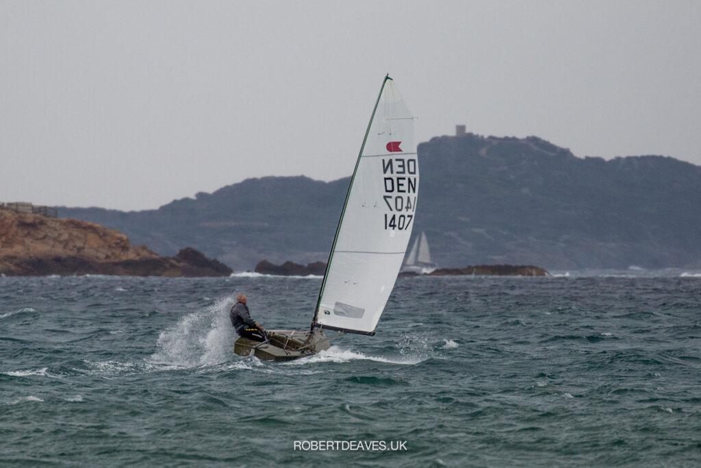 An OK Dinghy sailing off the beach, on a run.