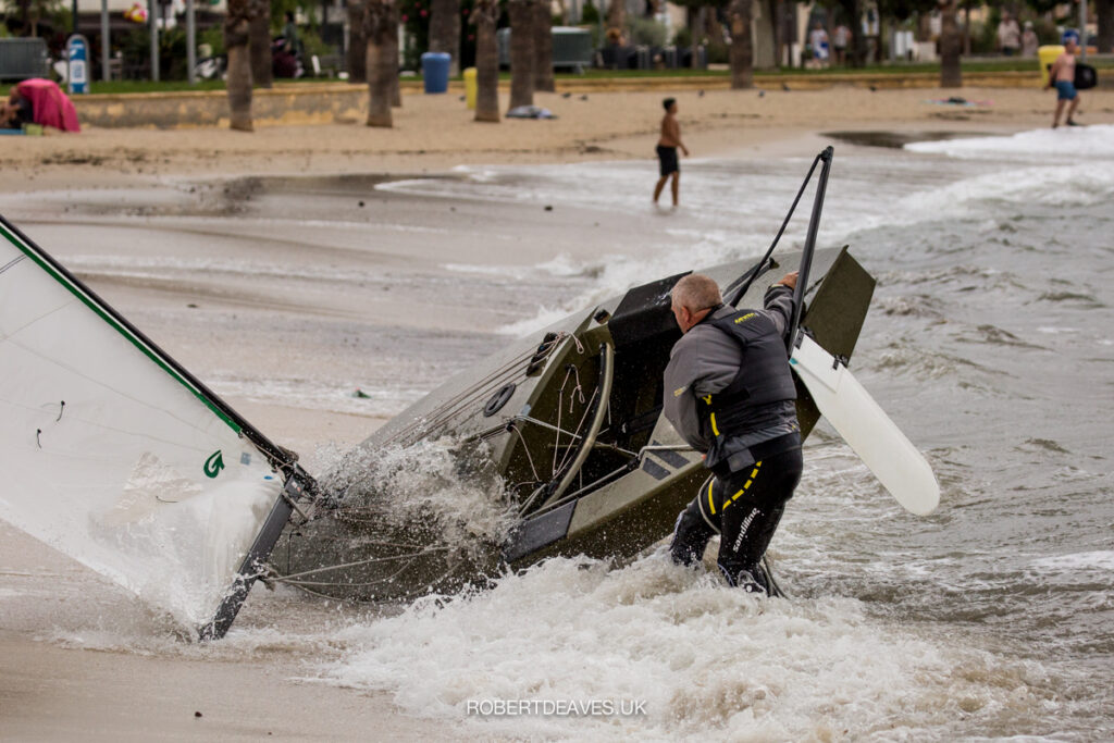 An OK dinghy being pushed by a wave onto the beach. The skipper trying to stop it from going onto the beach.