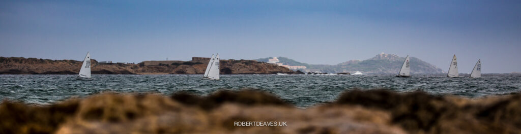 Shot from land, from ground-view, boats sailing upwind.