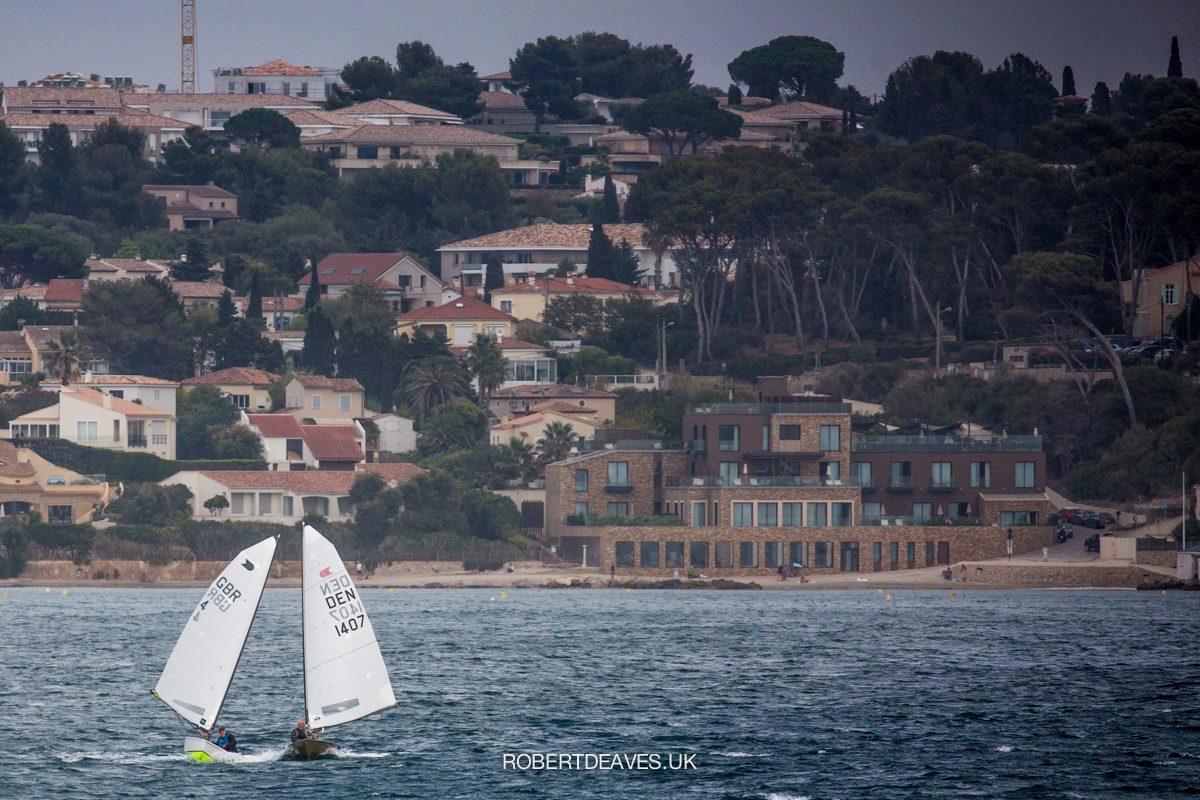 Two sailors on running downwind with the town in the background.