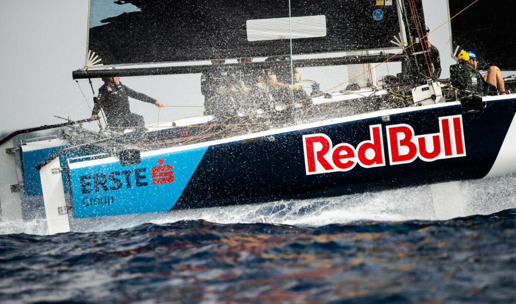 Red Bull Sailing Team making alot of spray as they go upwind.