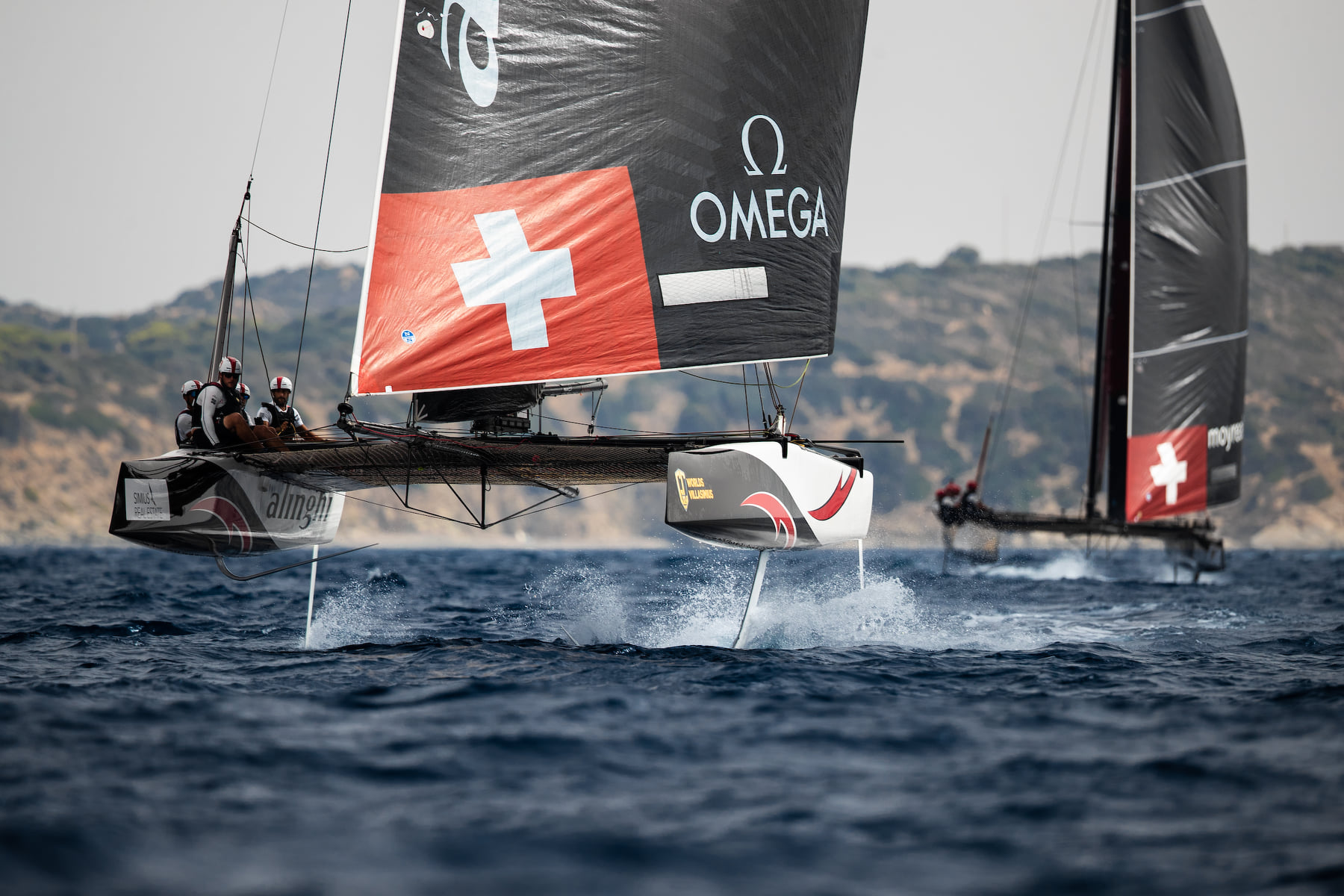 Two catamarans foiling downwind.