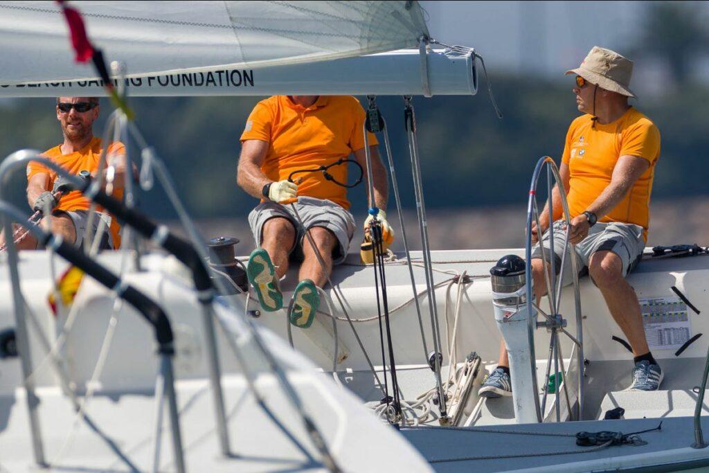 Johnie Berntsson steering, with 2 crew members hiking.