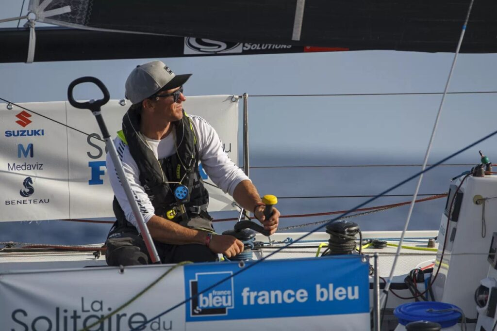 Xavier Macaire winding a winch handle, looking forward.