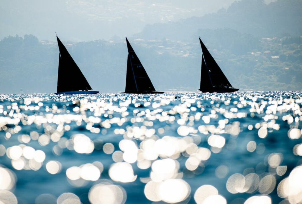 Three yachts in a line sailing upwind, sun glistening on the water.