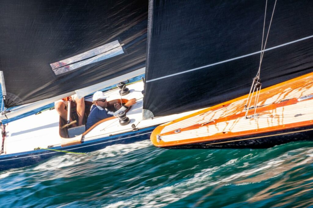 Two Six Metre yachts sailing next to each other upwind.