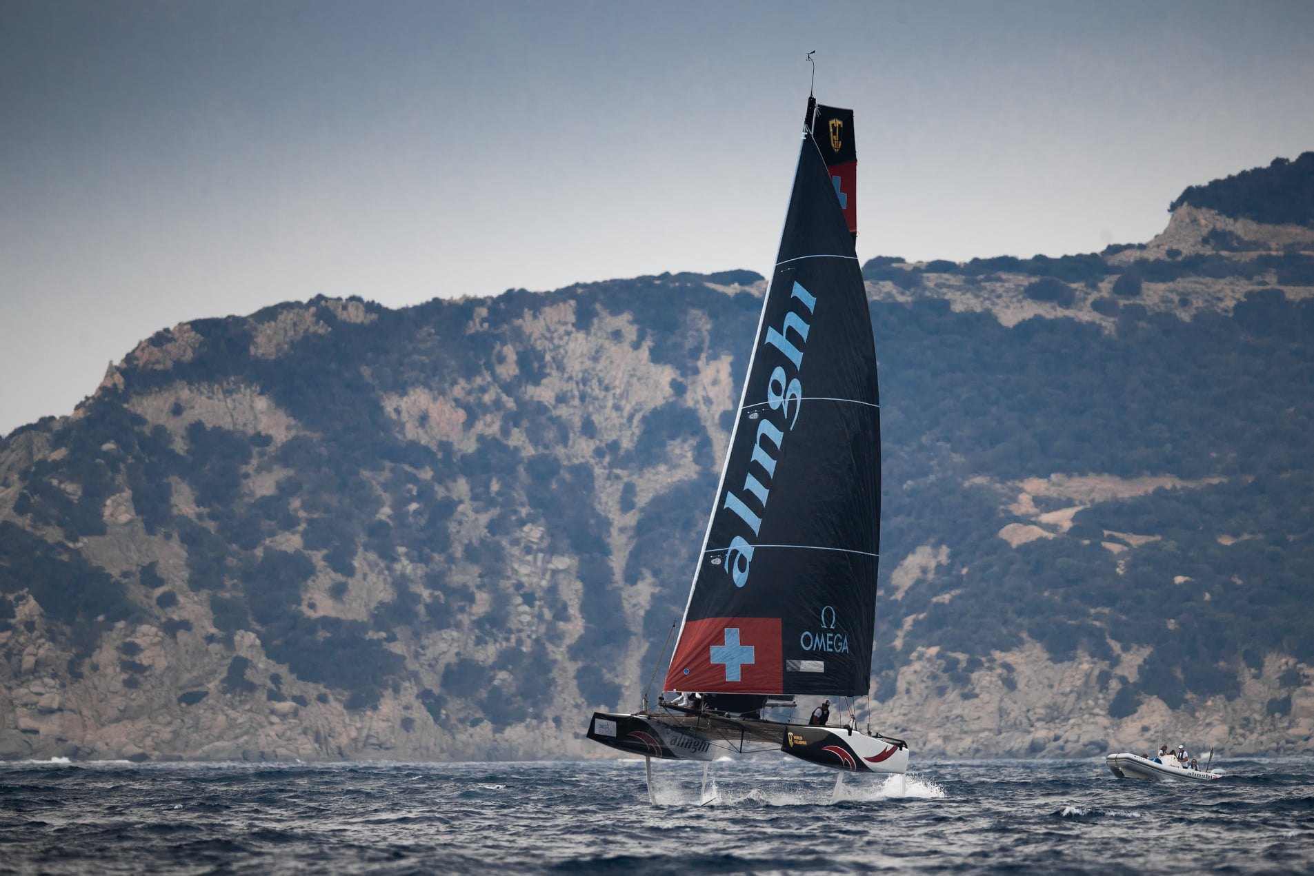 Alinghi foiling downwind with land (mountains) in background.