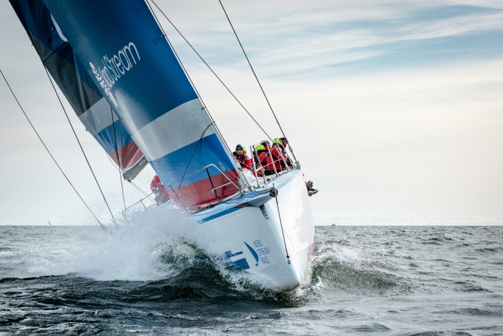 Russia sailing upwind in chop, crew sitting on the side.