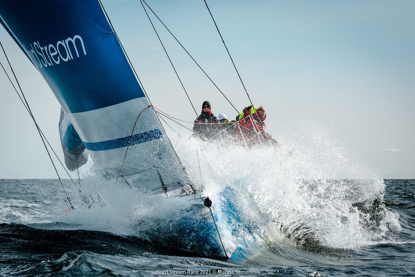 Finn boat sailing through chop, upwind.