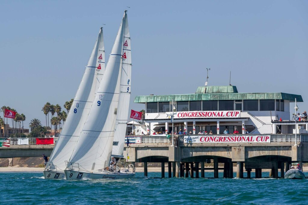 Two boats side by side at the pre-start sailing away from pier.