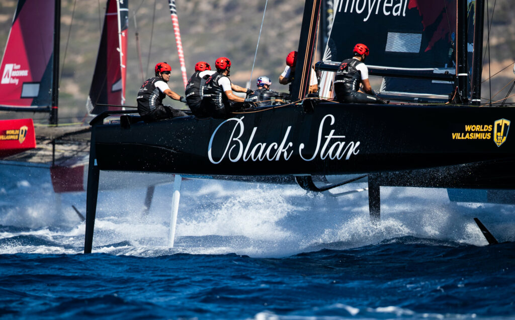 Black Star sailing upwind with a boat just behind her.